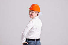 Young Blondie Architectures is Holding Rolled Architectural Plans. Young Architectures in Orange Safety Helmet is Holding Rolled Architectural Plans and Looks Royalty Free Stock Image