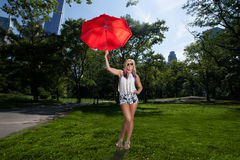 Young Blonde Athletic woman holding a Red Umbrella Royalty Free Stock Images