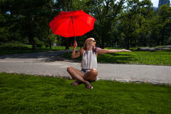 Young Blonde Athletic woman holding a Red Umbrella Stock Photography