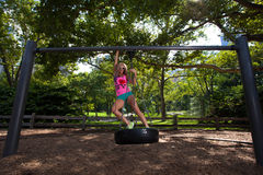 Young Blonde Athletic woman sitting on a tire swing. Young Blonde Athletic woman sitting and rocking on a tire swing in Central Park Stock Images