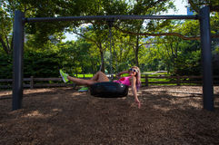 Young Blonde Athletic woman sitting on a tire swing Royalty Free Stock Image