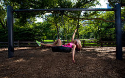 Young Blonde Athletic woman sitting on a tire swing Royalty Free Stock Photos