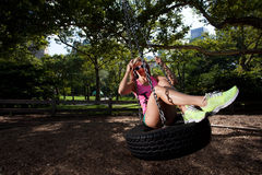 Young Blonde Athletic woman sitting on a tire swing Stock Photo