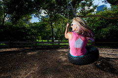 Young Blonde Athletic woman sitting on a tire swing Stock Image