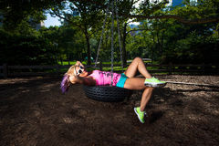 Young Blonde Athletic woman sitting on a tire swing Stock Images