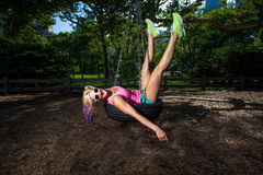 Young Blonde Athletic woman sitting on a tire swing Royalty Free Stock Photo