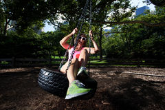 Young Blonde Athletic woman sitting on a tire swing Royalty Free Stock Photography