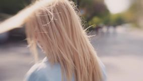 Young blonde attractive girl in a jeans jacket wondering down the streets, windy weather. Waving hair, cute smile. Young blonde European girl in a jeans jacket stock footage