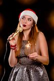 Young blonde attractive woman in red new year hat with microphone and sparkler. On singing the stage Stock Images