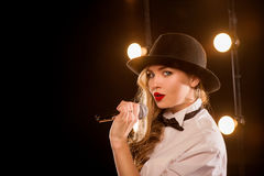 Young blonde attractive woman in white shirt, black hat Royalty Free Stock Image