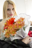 Young blonde beautiful woman with bunch of flowers Royalty Free Stock Photos