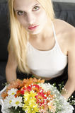 Young blonde beautiful woman with bunch of flowers Stock Photography