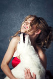 Young blonde beautiful young woman hugging huskies puppy dog. Red glamour dress Stock Photos