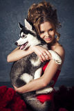 Young blonde beautiful young woman hugging huskies puppy dog. Red glamour dress Stock Images