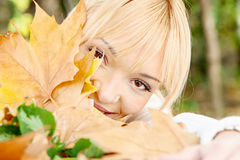 Young blonde behind the leaves. On summer day Stock Photos