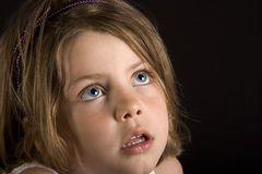 Young Blonde, Big Blue Eyes. Shot of a young blonde girl with blue blue eyes looking up, against a black background Royalty Free Stock Images