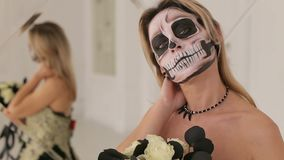 A young blonde in a black dress and makeup in the form of a skeleton. Halloween. A young blonde in a black dress with a bouquet of black flowers and makeup in stock video footage