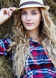 Young blonde  blue-eyed country girl in hat near haystacks Royalty Free Stock Images