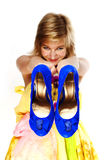 Young blonde with blue shoes. In their hands Stock Photography