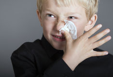 Young blonde boy with a cold and a tissue Royalty Free Stock Image
