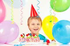 Young blonde boy in festive hat with birthday cake and balloons Stock Images