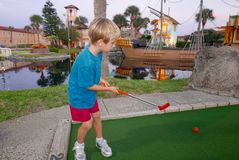 Young blonde boy playing miniature golf royalty free stock images