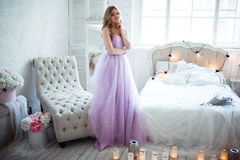 A young blonde bride in a magnificent purple dress is in the bedroom. In the room candles and bouquets of flowers. Stock Images