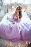 A young blonde bride in a magnificent purple dress sitting on the bed. In the room candles. Girl holds in the hands of Stock Photo