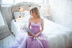 A young blonde bride in a magnificent purple dress sitting on the bed. In the room candles. Girl holds in the hands of. A young blonde bride in a magnificent Royalty Free Stock Photos