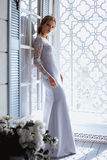 Young blonde bride woman in a light blue wedding dress. Fashion beauty portrait in interior Stock Photos