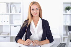 Young blonde business woman with laptop in the office.  Stock Photography