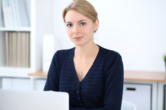 Young blonde business woman with laptop in the office. Business concept.  Stock Photography