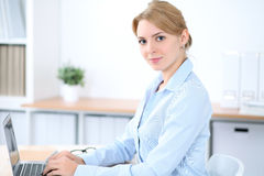 Young blonde business woman with laptop in the office. Business concept.  Stock Photo