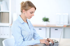 Young blonde business woman with laptop in the office. Business concept Royalty Free Stock Image