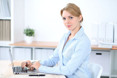 Young blonde business woman with laptop in the office. Business concept Stock Photo