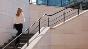 Young blonde business woman walks upstairs outside in a sunny day near office building.  stock video footage