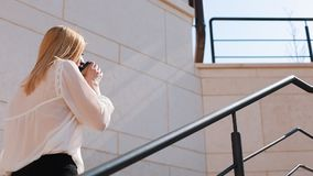 Young blonde business woman walks upstairs outside in a sunny day near office building.  stock footage