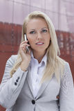 Young blonde businesswoman communicating on mobile phone against office building Stock Image