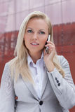 Young blonde businesswoman communicating on mobile phone against office building Royalty Free Stock Photos