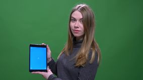 Young blonde businesswoman shows blue chroma screen of tablet isolated on green chromakey background. stock video