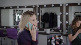 Young blonde businesswoman is using her smartphone during make-up in luxury beauty shop. Personal visagiste is applying stock video