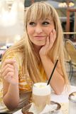 Young blonde in a cafe with latte macchiato Royalty Free Stock Image