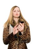 Young blonde calling. Young blonde in the fur coat calling royalty free stock photos