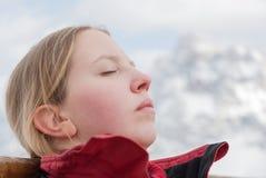 Young blonde Caucasian blonde woman girl sunbathing mountain ski snow sky mountain face close Stock Photos