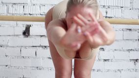 Sporty caucasian cute woman in leotard is doing bend down stretch exercises. Young blonde caucasian sportive woman with big blue eyes dressed in beige leotard is stock footage