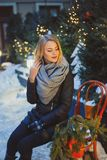 Young Blonde caucasian woman in black coat and gray scarf sitting on the bench Stock Image