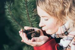 Young blonde woman holding Christmas tree pinecones