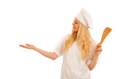 Young blonde chef points to copy space as she presents a new rec Royalty Free Stock Photos