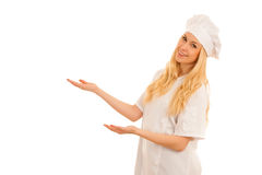 Young blonde chef points to copy space as she presents a new rec Royalty Free Stock Photo