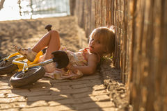 Young  blonde child girl in dress fallen from small balance bike. Warm sunset light. Family summer travel vacations a Royalty Free Stock Photo